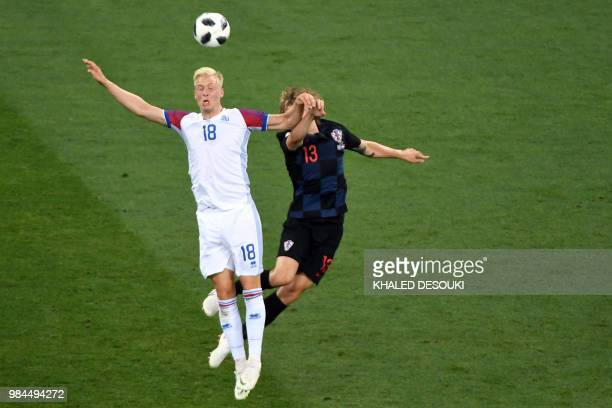 Croatia's defender Tin Jedvaj heads the ball with Iceland's defender Hordur Magnusson during the Russia 2018 World Cup Group D football match between...