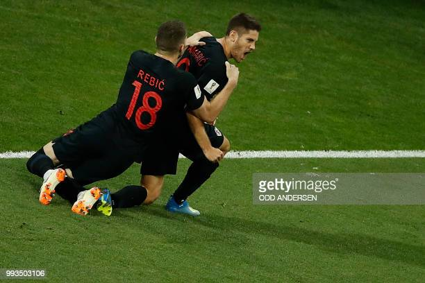 TOPSHOT Croatia's forward Andrej Kramaric is congratulated by Croatia's forward Ante Rebic after scoring the equalizer during the Russia 2018 World...