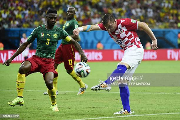 Croatia's forward Ivica Olic kicks the ball marked by Cameroon's defender Nicolas Nkoulou during a Group A football match between Cameroon and...