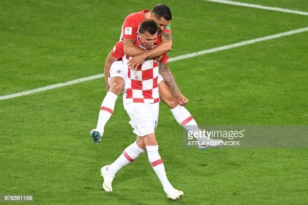 TOPSHOT Croatia's forward Mario Mandzukic and Croatia's defender Dejan Lovren celebrate an own goal by Nigeria's midfielder Oghenekaro Etebo during...