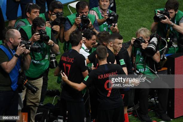 TOPSHOT Croatia's forward Mario Mandzukic and Croatia's midfielder Ivan Rakitic speak to AFP photographer Yuri Cortez after falling on him with...