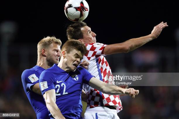 Croatia's forward Mario Mandzukic and Finland's defender Albin Granlund go for a header during the FIFA World Cup 2018 qualification football match...