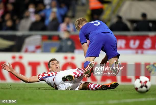 Croatia's forward Mario Mandzukic and Finland's Juhani Ojala collide during the FIFA World Cup 2018 qualification football match between Croatia and...