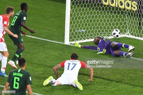 TOPSHOT Croatia's forward Mario Mandzukic dives and Nigeria's midfielder Oghenekaro Etebo scores an own goal against teammate Nigeria's goalkeeper...
