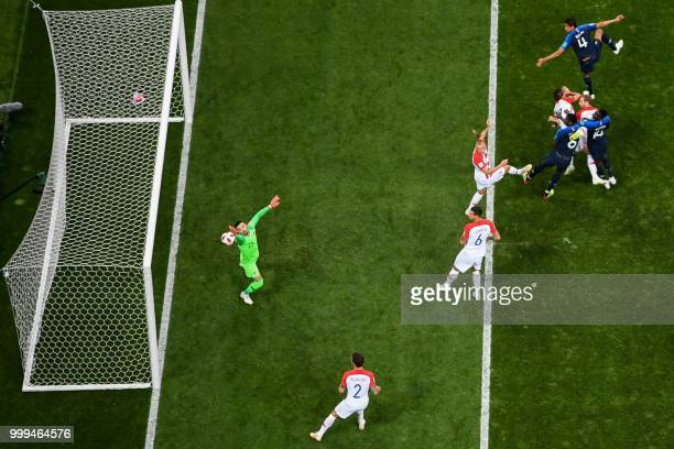 Croatia's forward Mario Mandzukic heads the ball and scores an own goal after France's forward Antoine Griezmann shot a free kick during the Russia...