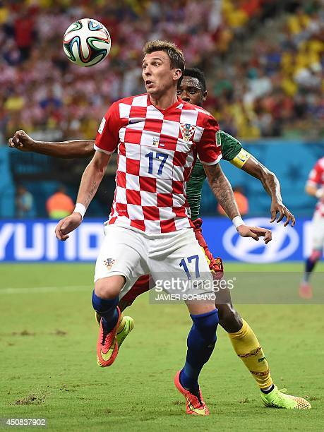 Croatia's forward Mario Mandzukic is watched by Cameroon's defender Nicolas Nkoulou as he controls the ball during the Group A football match between...
