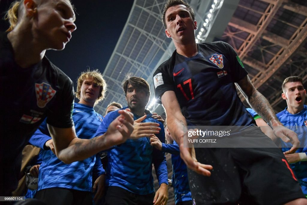 TOPSHOT - Croatia's forward Mario Mandzukic (C) offers to help AFP photographer Yuri Cortez after he fell on him with teammates while celebrating their second goal during the Russia 2018 World Cup semi-final football match between Croatia and England at the Luzhniki Stadium in Moscow on July 11, 2018. (Photo by Yuri CORTEZ / AFP) / RESTRICTED