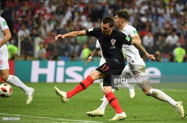 Croatia's forward Mario Mandzukic scores his team's second goal past England's defender John Stones during the Russia 2018 World Cup semi-final...