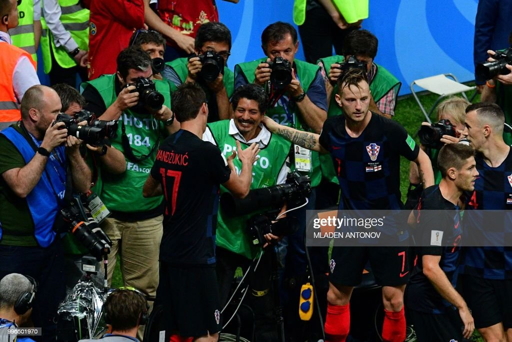 TOPSHOT - Croatia's forward Mario Mandzukic (L) shakes hands with AFP photographer Yuri Cortez (C) after falling on him with teammates while celebrating their second goal during the Russia 2018 World Cup semi-final football match between Croatia and England at the Luzhniki Stadium in Moscow on July 11, 2018. (Photo by Mladen ANTONOV / AFP) / RESTRICTED