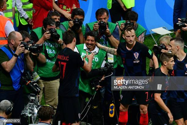 TOPSHOT Croatia's forward Mario Mandzukic shakes hands with AFP photographer Yuri Cortez after falling on him with teammates while celebrating their...