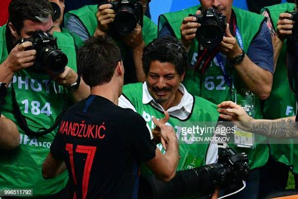 Croatia's forward Mario Mandzukic shakes hands with AFP photographer Yuri Cortez after falling on him with teammates while celebrating their second...