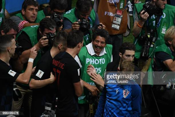 Croatia's forward Mario Mandzukic speaks with AFP photographer Yuri Cortez after falling on him with teammates while celebrating their second goal...