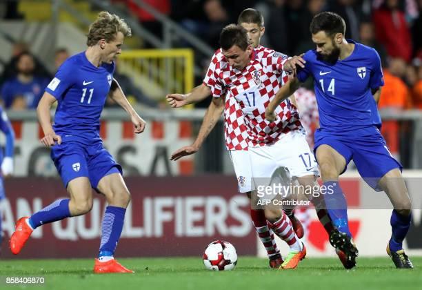 Croatia's forward Mario Mandzukic vies with Finland's midfielder Tim Sparv and midfielder Rasmus Schuller during the FIFA World Cup 2018...