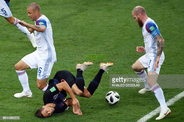 Croatia's forward Marko Pjaca falls after challenging Iceland's defender Ragnar Sigurdsson and Iceland's midfielder Aron Gunnarsson during the Russia...