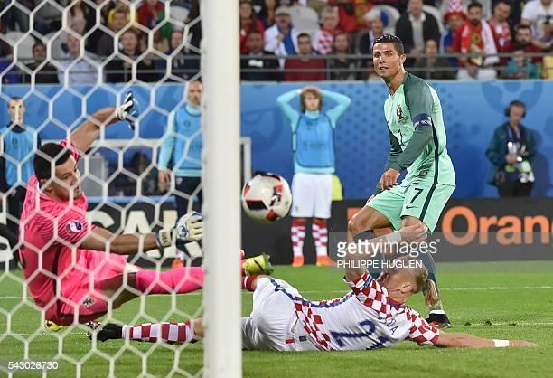 TOPSHOT Croatia's goalkeeper Danijel Subasic and Croatia's defender Domagoj Vida try to stop a goal beside Portugal's forward Cristiano Ronaldo...