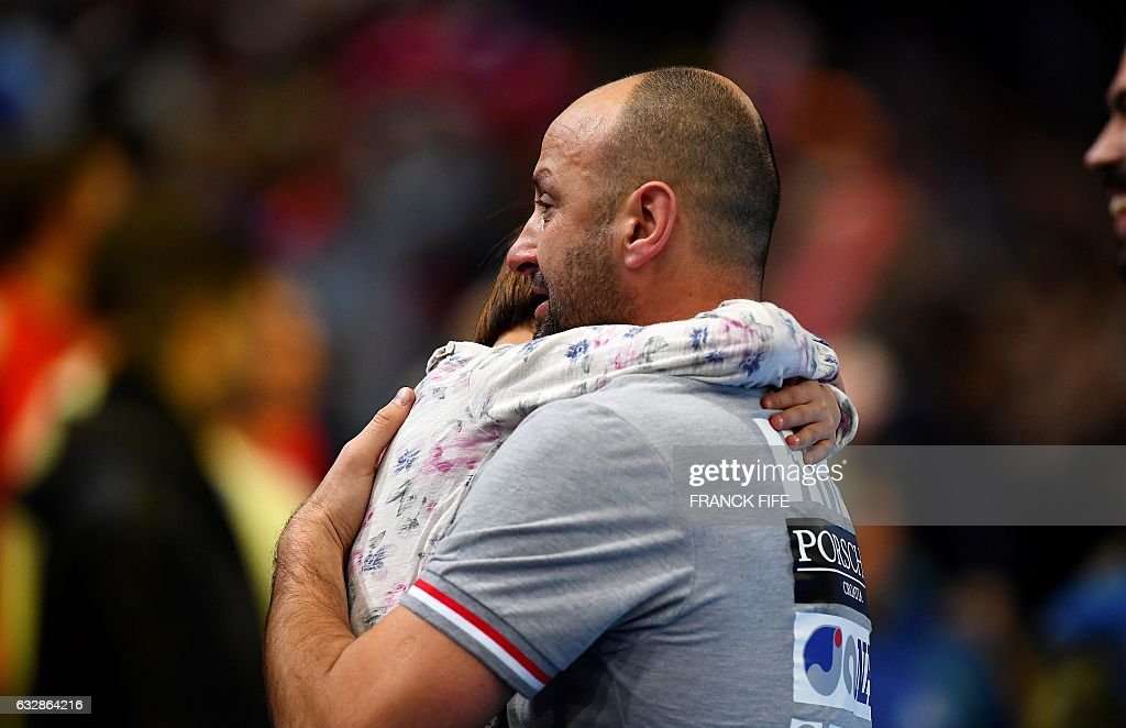 Croatia's head coach Zeljko Babic carries a child after losing the 25th IHF Men's World Championship 2017 semi-final handball match Croatia vs Norway on January 27, 2017 at the Accorhotels Arena in Paris. / AFP / FRANCK