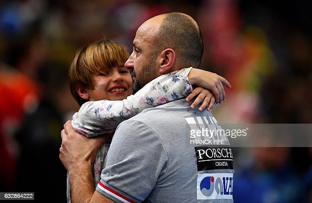 Croatia's head coach Zeljko Babic carries a child after losing the 25th IHF Men's World Championship 2017 semifinal handball match Croatia vs Norway...