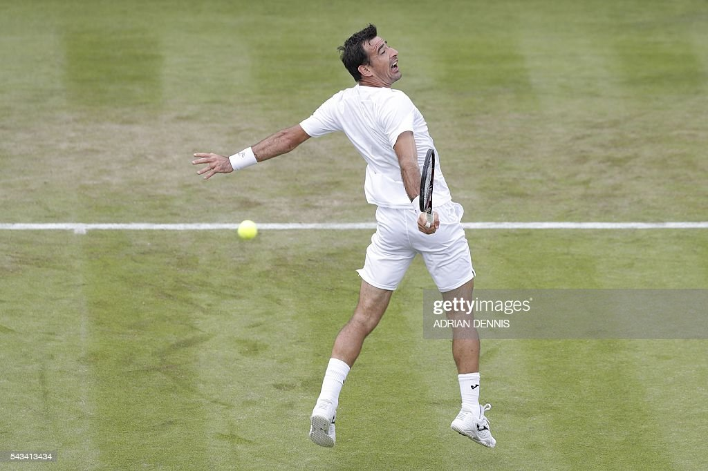 TOPSHOT - Croatia's Ivan Dodig returns against Czech Republic's Tomas Berdych during their men's singles first round match on the second day of the 2016 Wimbledon Championships at The All England Lawn Tennis Club in Wimbledon, southwest London, on June 28, 2016. / AFP / ADRIAN