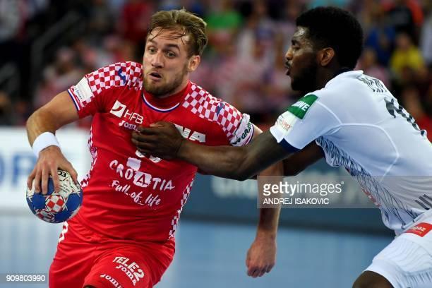 Croatia's Luka Cindric vies with France's Dika Mem during the group I match of the Men's 2018 EHF European Handball Championship between Croatia and...