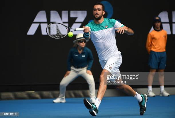 Croatia's Marin Cilic hits a return against Spain's Pablo Carreno Busta during their men's singles fourth round match on day seven of the Australian...