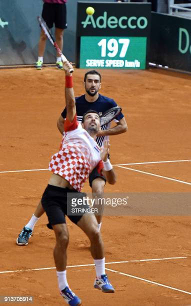 Croatia's Marin Cilic looks at Ivan Dodig as he hits a return against Canada's Daniel Nestor and Vasek Pospis during the Davis Cup World Group fiorst...