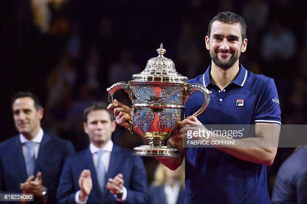 Croatia's Marin Cilic poses with the trophy after winning the final match against Japan's Kei Nishikori at the Swiss Indoors ATP 500 tennis...
