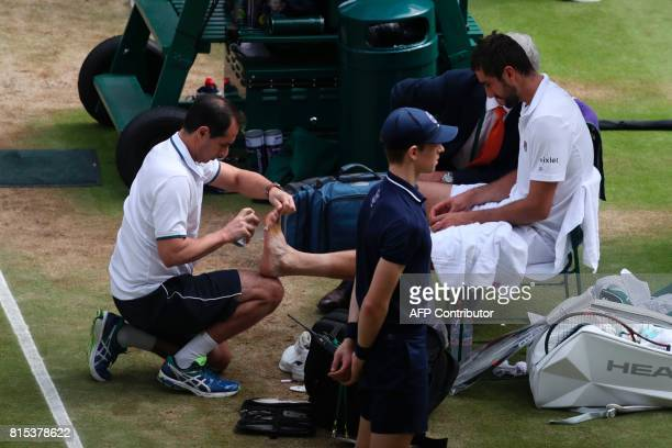 Croatia's Marin Cilic receives treatment on his foot during a medical time-out during his men's singles final match against Switzerland's Roger...