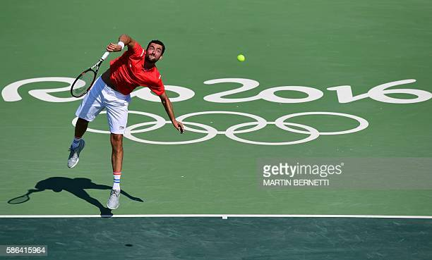 Croatia's Marin Cilic serves the ball to Bulgaria's Grigor Dimitrov during their men's first round singles tennis match at the Olympic Tennis Centre...
