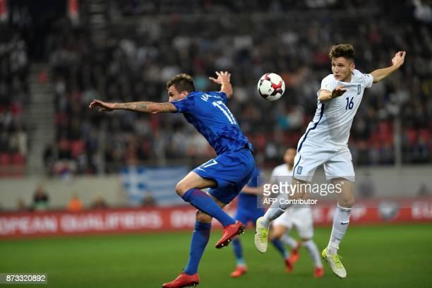 Croatia's Mario Mandzukic vies with Greece's Panagiotis Retsos during the World Cup 2018 playoff football match Greece vs Croatia on November 12 2017...