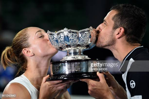 Croatia's Mate Pavic and Canada's Gabriela Dabrowski kiss the winners' trophy after beating Hungary's Timea Babos and India's Rohan Bopanna in their...