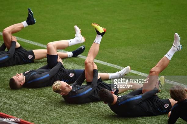 Croatia's midfielder Ivan Rakitic and Croatia's goalkeeper Lovre Kalinic take part in a training session at Anfield stadium in Liverpool on June 2...