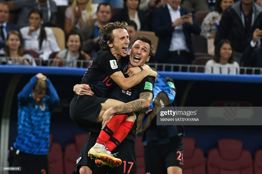 TOPSHOT - Croatia's midfielder Luka Modric and Croatia's forward Mario Mandzukic celebrate their win at the end of the Russia 2018 World Cup semi-final football match between Croatia and England at the Luzhniki Stadium in Moscow on July 11, 2018. - Croatia will play France in the World Cup final after they beat England 2-1 in extra-time on Wednesday thanks to a Mario Mandzukic goal in the second period of extra-time. (Photo by MANAN VATSYAYANA / AFP) / RESTRICTED