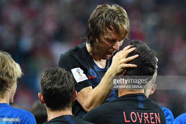 Croatia's midfielder Luka Modric celebrates with teammate Croatia's defender Dejan Lovren after Croatia won the penalty shootout at the end of the...