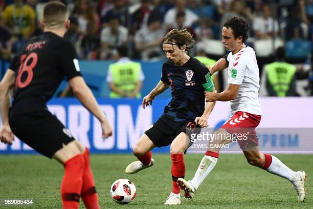 Croatia's midfielder Luka Modric challenges Denmark's midfielder Thomas Delaney during the Russia 2018 World Cup round of 16 football match between...