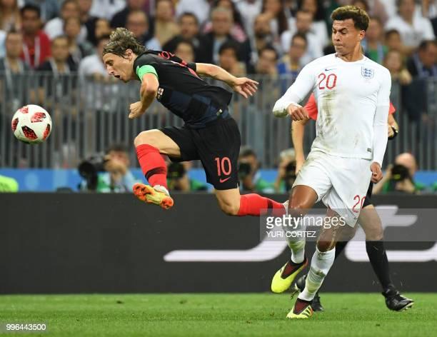 Croatia's midfielder Luka Modric challenges England's midfielder Dele Alli during the Russia 2018 World Cup semifinal football match between Croatia...