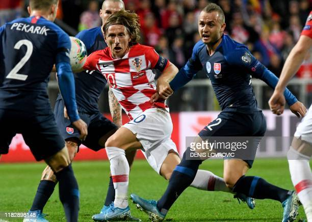 Croatia's midfielder Luka Modric fights for the ball with Slovakia's defender Peter Pekarik , Stanislav Lobotka during the Euro 2020 Group E football...