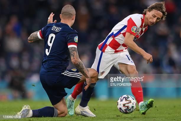 Croatia's midfielder Luka Modric is marked by Scotland's forward Lyndon Dykes during the UEFA EURO 2020 Group D football match between Croatia and...