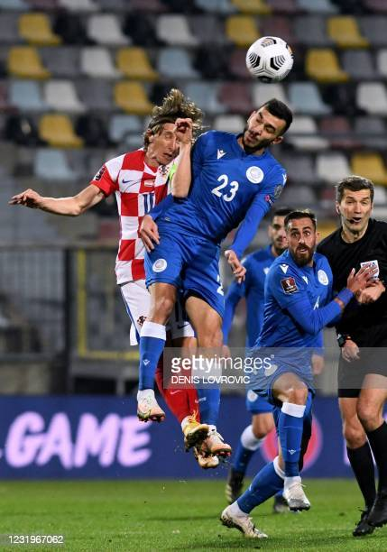 Croatia's midfielder Luka Modric jumps for the ball with Cyprus mifielder Ioannis Pittas during the FIFA World Cup Qatar 2022 qualification Group H...