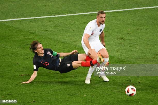 TOPSHOT Croatia's midfielder Luka Modric vies for the ball with England's midfielder Jordan Henderson during the Russia 2018 World Cup semifinal...