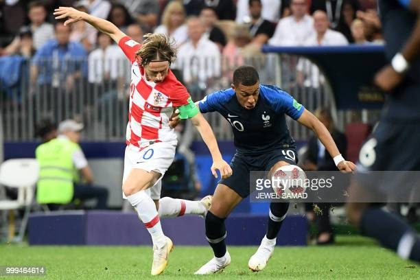 TOPSHOT Croatia's midfielder Luka Modric vies for the ball with France's forward Kylian Mbappe during their Russia 2018 World Cup final football...