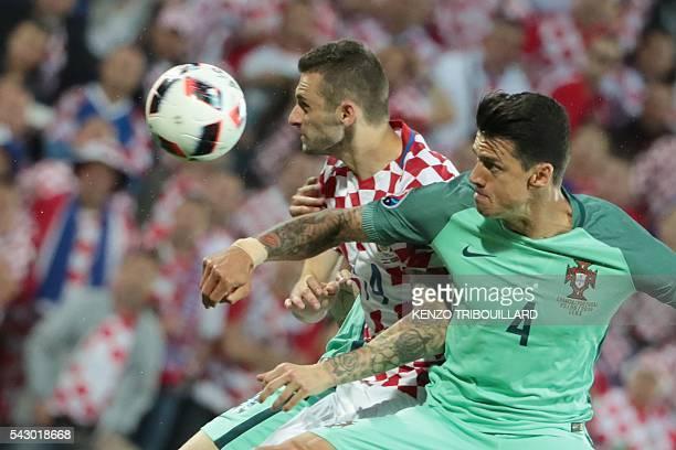 TOPSHOT Croatia's midfielder Marcelo Brozovic and Croatia's midfielder Ivan Perisic jump for the ball during the round of sixteen football match...