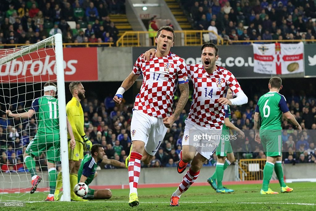 Croatia's midfielder Mario Mandzukic (C) celebrates scoring his team's first goal with Croatia's forward Duje Cop during the friendly international football match between Northern Ireland and Croatia at Windsor Park in Belfast on November 15, 2016. / AFP / PAUL