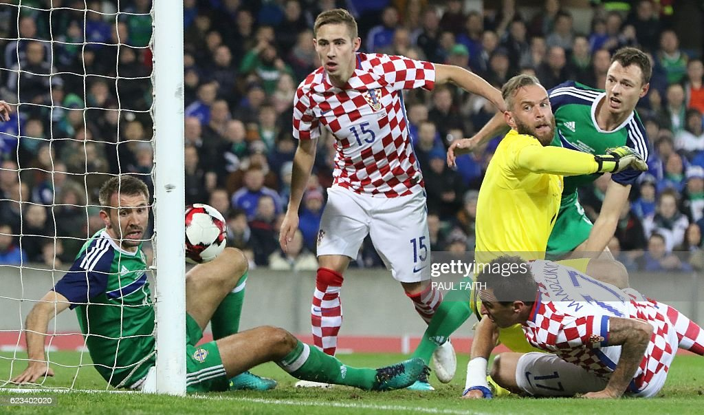 TOPSHOT - Croatia's midfielder Mario Mandzukic (R) scores his team's first goal past Northern Ireland's goalkeeper Alan Mannus during the friendly international football match between Northern Ireland and Croatia at Windsor Park in Belfast on November 15, 2016. / AFP / PAUL