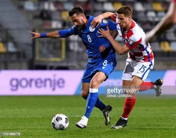 Croatia's midfielder Mario Pasalic fights for the ball with Cyprus' midfielder Charis Kyriakou during the FIFA World Cup Qatar 2022 qualification...