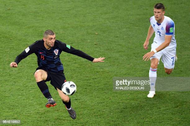 TOPSHOT Croatia's midfielder Mateo Kovacic challenges Iceland's midfielder Johann Gudmundsson during the Russia 2018 World Cup Group D football match...