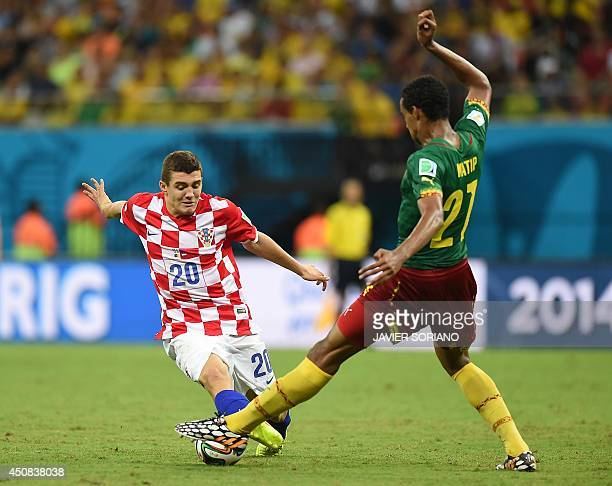 Croatia's midfielder Mateo Kovacic is tackled by Cameroon's midfielder Joel Matip during the Group A football match between Cameroon and Croatia at...