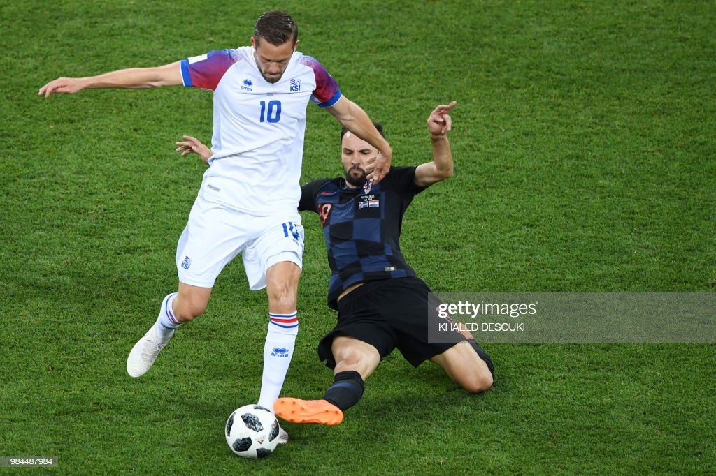 TOPSHOT - Croatia's midfielder Milan Badelj (back) challenges Iceland's midfielder Gylfi Sigurdsson during the Russia 2018 World Cup Group D football match between Iceland and Croatia at the Rostov Arena in Rostov-On-Don on June 26, 2018. (Photo by Khaled DESOUKI / AFP) / RESTRICTED