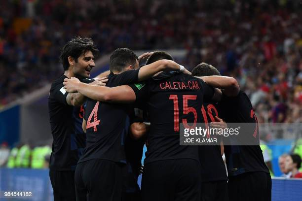 TOPSHOT Croatia's midfielder Milan Badelj is congratulated by teammates after scoring the opening goal during the Russia 2018 World Cup Group D...
