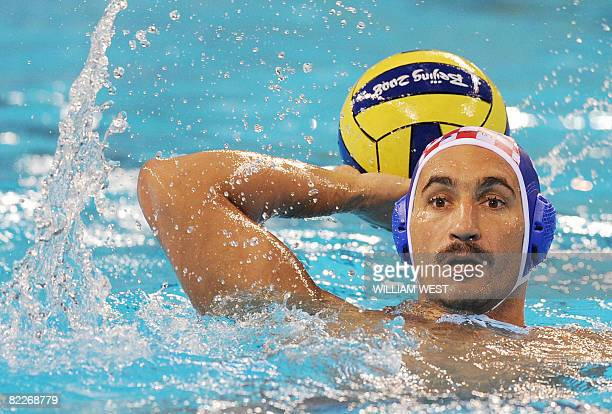 Croatia's Pavo Markovic prepares to throw the ball past Serbia's defenders during their men's preliminary roung group B water polo match at the 2008...