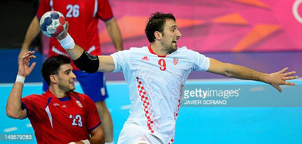 Croatia's pivot Igor Vori jumps to shoot next to Serbia's Nenad Vuckovic during the men's preliminaries Group B handball match Serbia vs Croatia for...
